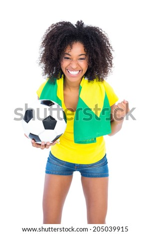 Pretty football fan holding brazilian flag cheering at camera on white background