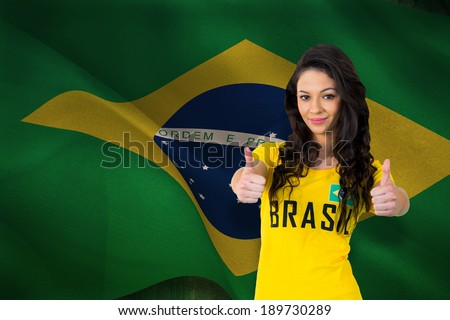 Pretty football fan in brasil tshirt against digitally generated brazil national flag - stock photo