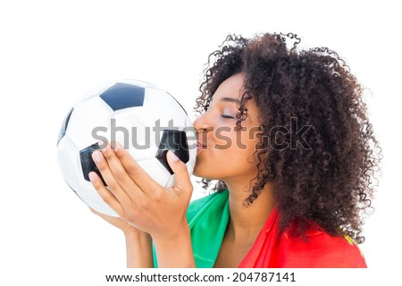 Pretty football fan with portugal flag kissing ball on white background