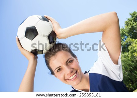 Pretty football player smiling at camera on a sunny day - stock photo