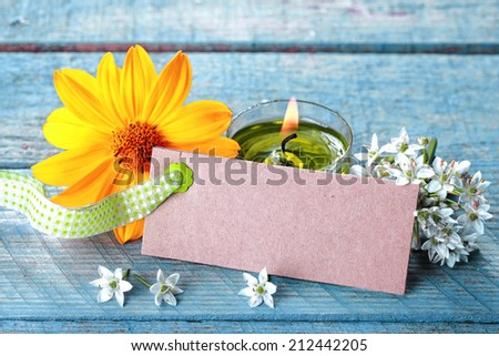 Pretty fresh country spa background with a blank label tied by a decorative checked green and white ribbon with white blossom, a yellow sunflower and burning candle for aromatherapy treatment - stock photo