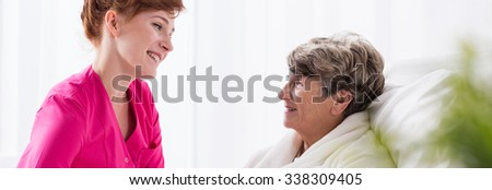 Pretty friendly nurse spending time with older patient - stock photo