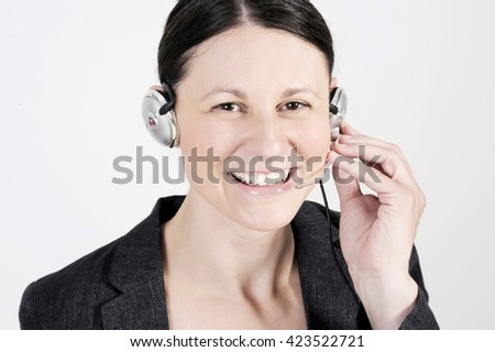 Pretty friendly officer woman with headset in a call center smiling and speaking with the client. - stock photo