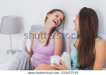 Pretty friends chatting over coffee in bed and laughing - stock photo