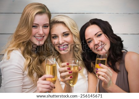 Pretty friends drinking champagne together against painted blue wooden planks