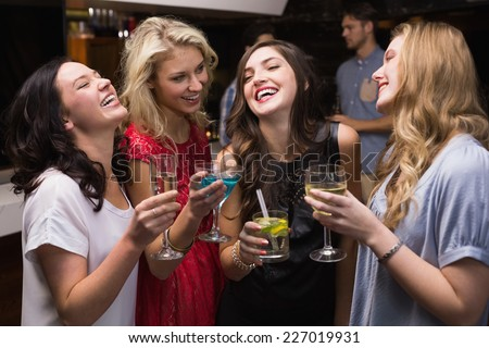 Pretty friends having a drink together at the bar - stock photo