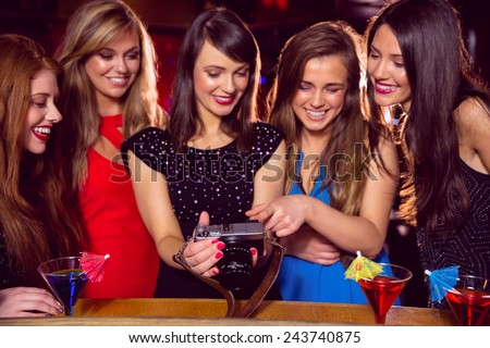 Pretty friends looking at camera together at the nightclub