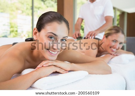 Pretty friends lying on massage tables with hot stones on their backs in the health spa - stock photo