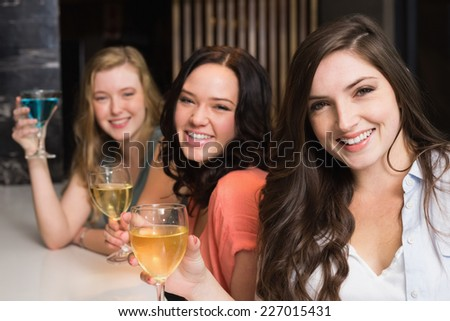 Pretty friends meeting up for a drink at the bar