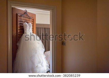 Pretty frilly wedding gown hanging on hotel room door. - stock photo