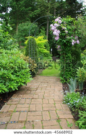 Pretty garden path covered by an arbor in springtime. - stock photo