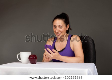 Pretty girl after a workout using her smart fone for texting reading - stock photo