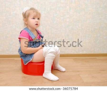 Pretty girl and red potty on wooden  floor - stock photo