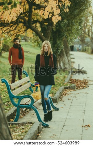 Pretty girl beautiful woman dating with bearded man hipster with beard near bench outdoors in autumn park on natural background