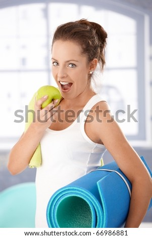 Pretty girl biting an apple after exercising in gym.? - stock photo