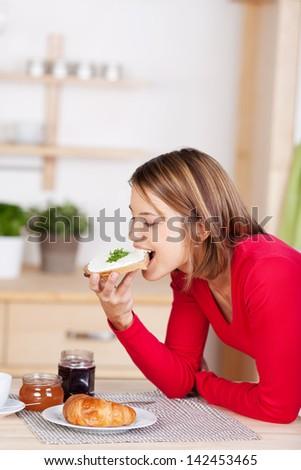 Pretty girl biting into a slice of bread at breakfast - stock photo