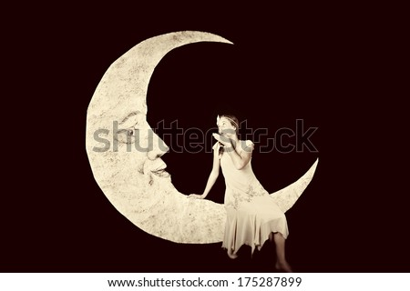 Pretty girl blowing kiss to vintage paper moon - stock photo