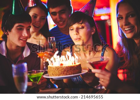 Pretty girl blowing on candles on birthday cake at party