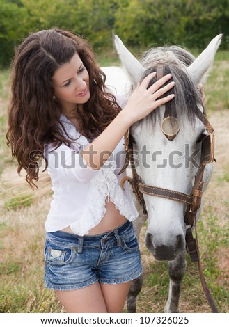 Pretty girl caring for her horse in a meadow - stock photo