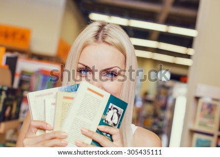 Pretty girl chooses books in library/bookshop - stock photo