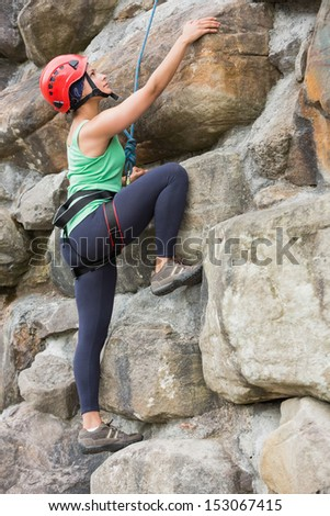 Pretty girl climbing rock face wearing safety gear - stock photo