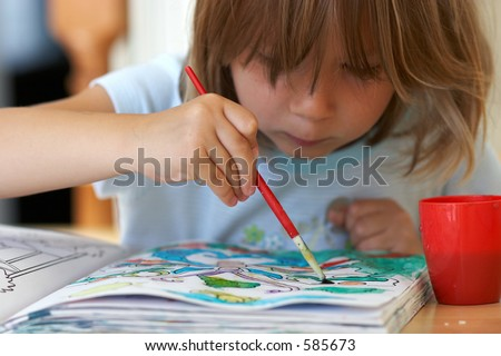 Pretty girl coloring a book - stock photo