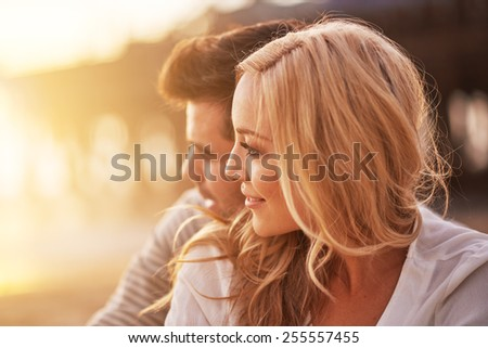 pretty girl cuddling with boyfriend on beach at santa monica with shallow depth of field and bright warm lens flare - stock photo