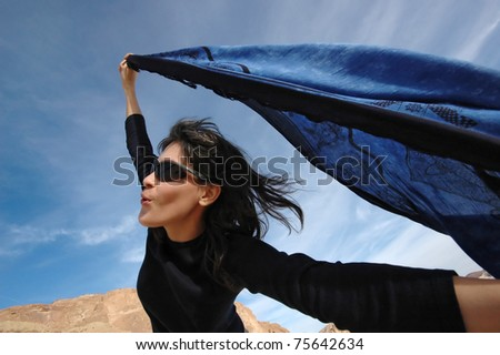 Pretty girl dancing with a blue shawl on a windy day. - stock photo