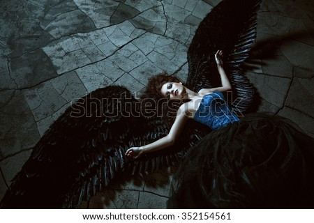 Pretty girl-demon with black wings behind her back - stock photo