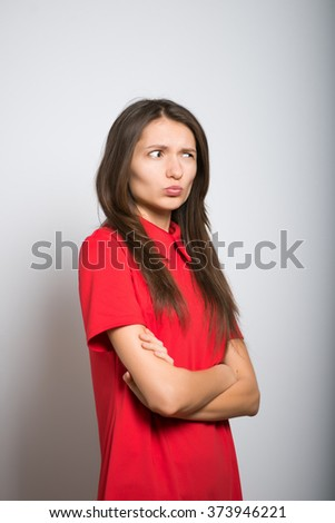 pretty girl dissatisfied with folded hands on a gray background