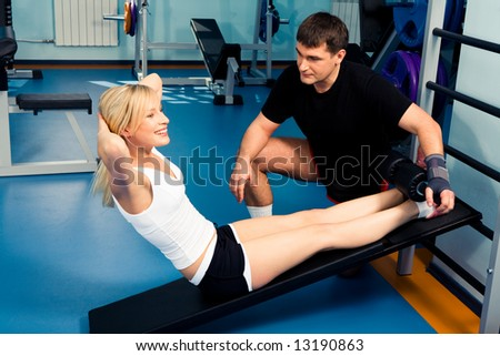 Pretty girl doing exercise with her personal trainer near by
