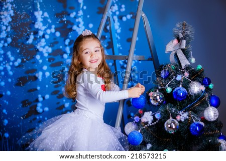 pretty girl dress up Christmas tree. blue accent decor - stock photo