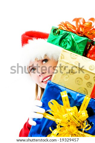 pretty girl dressed as Santa hiding behind the Christmas presents - stock photo