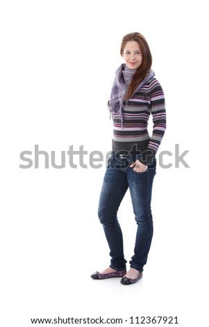 Pretty girl dressed for autumn, standing with hands in pocket, smiling at camera. - stock photo