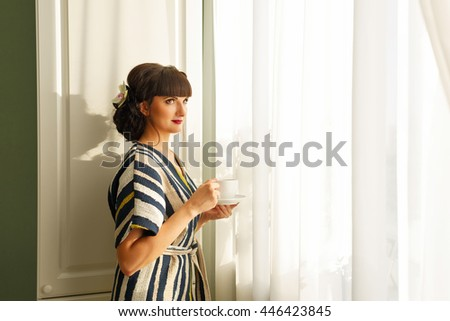 Pretty girl drinking morning coffee by the window. Good morning