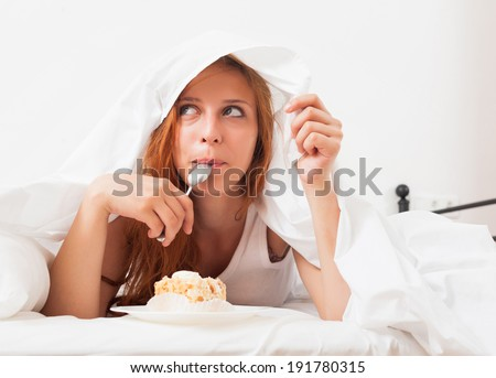 Pretty girl eating biscuit in her bed - stock photo