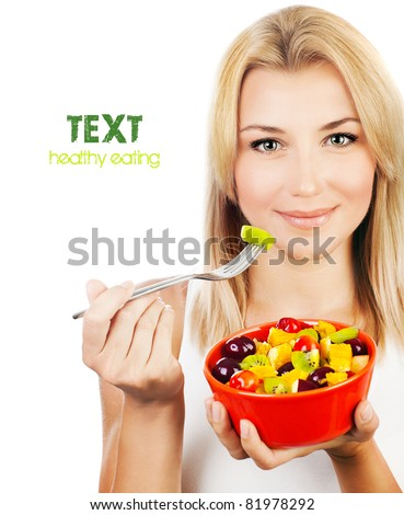 Pretty girl eating fruit salad, healthy fresh breakfast, dieting and health care concept - stock photo