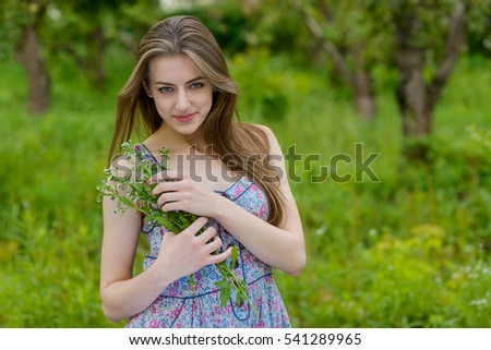 Pretty girl embraces nice bouquet of camomiles. Beauty looks in the camera with big blue eyes and pleased face.