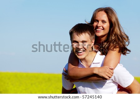Pretty girl embracing handsome boyfriend while both laughing and looking at camera - stock photo