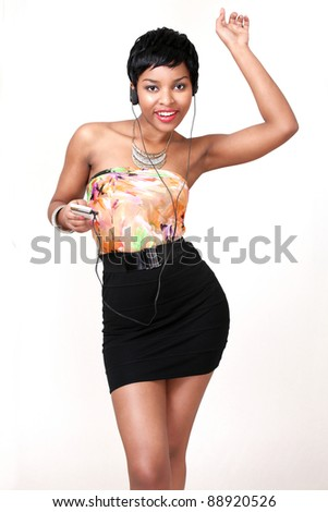 Pretty girl enjoying music on a handheld portable device with headphones - stock photo