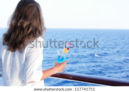 pretty girl enjoys traveling on a ship at sea - stock photo