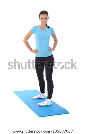 Pretty girl exercising on mattress, smiling. - stock photo