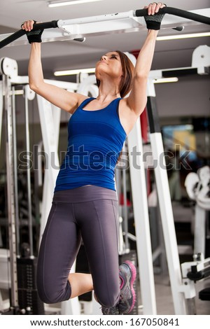 Pretty girl focused on doing some bar pull ups at the gym - stock photo