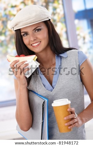 Pretty girl having club sandwich and coffee, smiling, looking at camera.?
