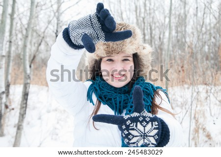 Pretty girl having fun outdoor, making frame with hands, taking picture with unrealistic camera, winter time - stock photo