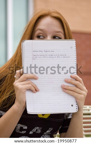Pretty girl hiding behind her note pad