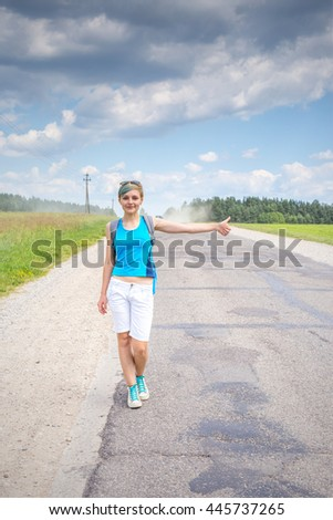 Pretty girl hitchhiking along the road