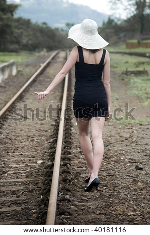 Pretty girl hitching a lift - stock photo