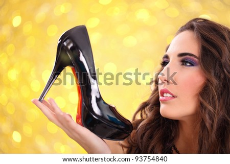 pretty girl holding a black high heel shoe in her hand and looking at it - stock photo