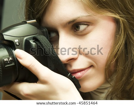 pretty girl holding a camera in the hands